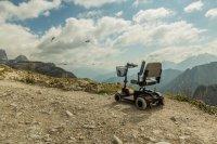 קלנועית מיני מתקפלת עם סל מקדימה על רקע של נוף עוצר נשימה