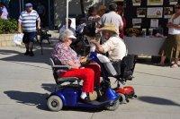 שני נשים מבוגרות נוסעות בקלנועית אחת לצד שנייה