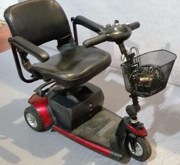 קלנועית אדומה עם סל מקדימה ומושב עם זוג ידיות