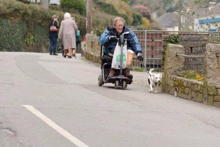 אדם בגיל השלישי נוסע בקלנועית מיני ולצידו כלב