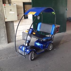 קלנועית בצבע כחול עם מושב משותף ארגז מאחורה סל מקידמה ומקום למגן רוח