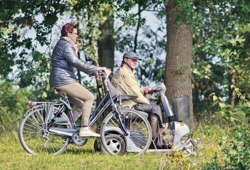 אדם מבוגר על קלנועית אפורה לצידו אישה על אופניים