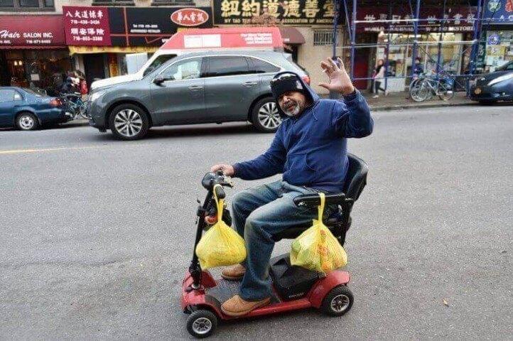 אדם מבוגר נוסע בקלנועית ומנוף לשלום
