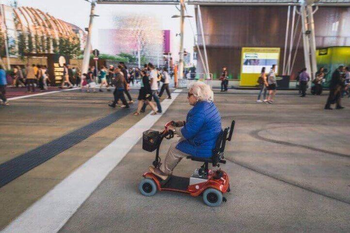 אישה מבוגרת על קלנועית מיני אדומה