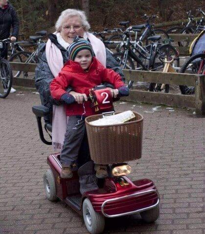 אישה מבוגרת מחזיקה ילדה קטנה על קלנועית מיני אדומה עם סל מקדימה
