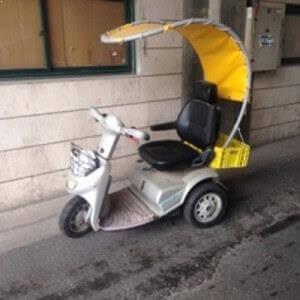 קלנועית בצבע בהיר עם גגון בצבע צהוב וסל מקדימה