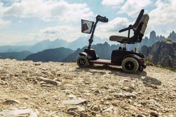 קלנועית יחיד עם סלסלת מוצרים נוסעת על שטח הררי